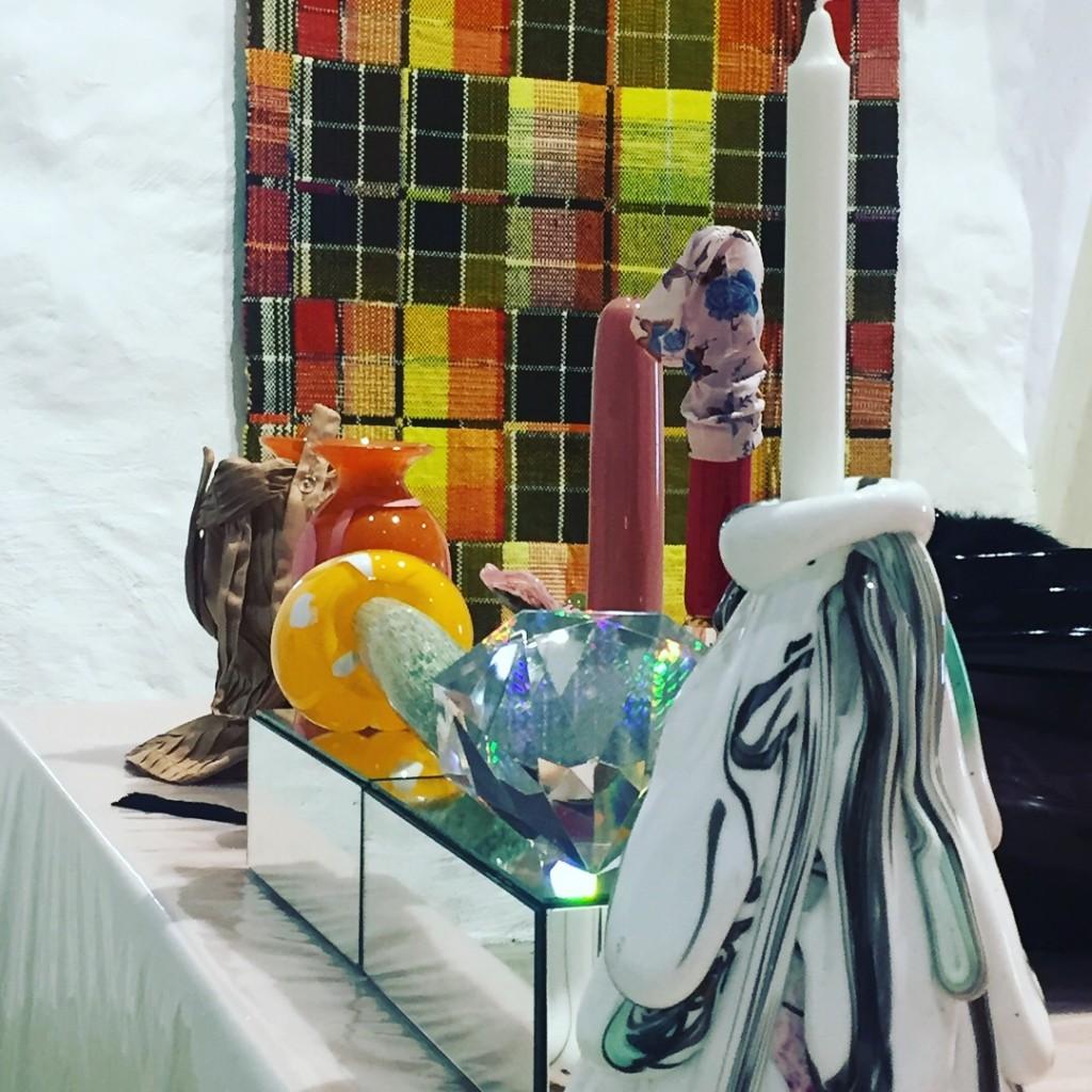 Installationsbild-Åsa Jungnelius glasobjekt i förgrunden. Josefin Gäfverts matta:Experiment genom en kökshandduk.